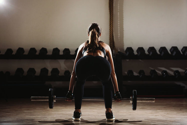 Woman Lifting Barbells In Gym