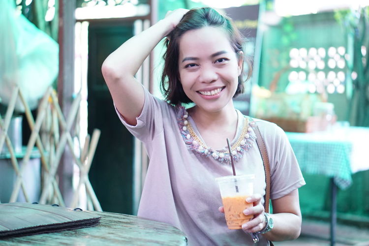 Portrait of smiling young woman having drink in cafe