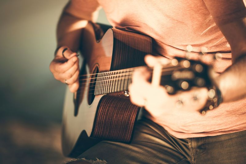 Caucasian Guitarist Playing Acoustic Guitar. Closeup Music String Instrument Theme. Acoustic Guitar Adult Adults Only Close-up Day Guitar Holding Human Body Part Human Hand Indoors  Leisure Activity Lifestyles Men Midsection Music Musical Instrument Musical Instrument String Musician One Person People Playing Plucking An Instrument Real People Rockman