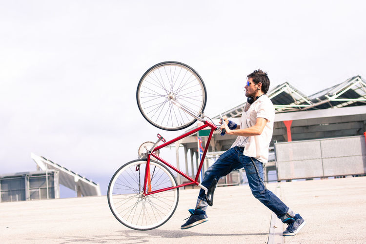 Man playing with a fixed bicycle. Barcelona, Spain Activity Architecture Beard Bicycle Casual Clothing City Cycling Day Fixed Full Length Holding Jeans Leisure Activity Lifestyles Men Mode Of Transportation One Person Outdoors Riding Sport Transportation Young Adult Young Men EyeEmNewHere