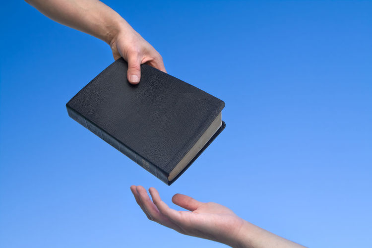 Close-up of hands with bible against blue background