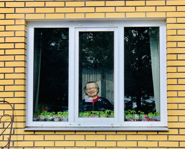 Portrait of woman seen through window of house