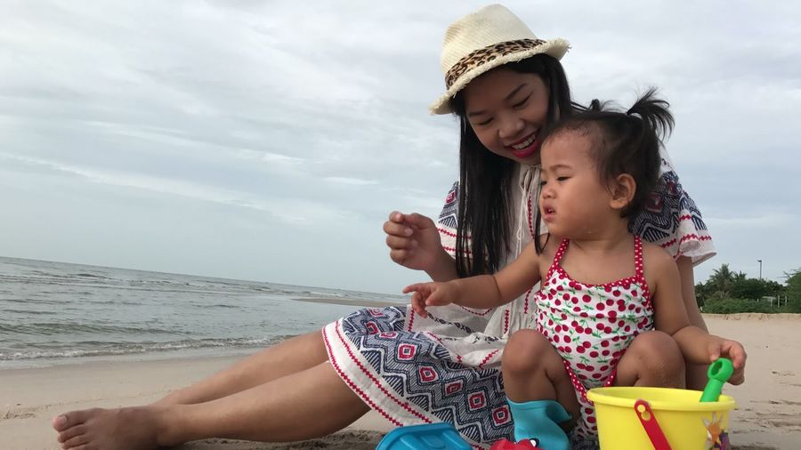 Smiling mother sitting with baby girl playing on shore at beach