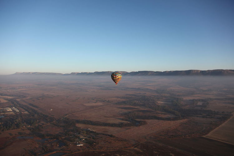 Hot air balloon flying over landscape against clear blue sky