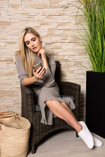 Full length of beautiful woman in dress sitting on chair while using phone at home