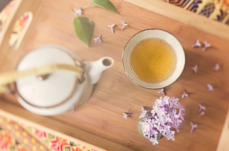 Overhead image of a Japanese teapot and cup with lilac flowers on a wooden tray Afternoon Tea Close-up Cup Flower Food And Drink Japanese Tea Lilac No People Overhead View Petal Quiet Moments Refreshment Selective Focus Still Life Table Tea Teapot Teatime