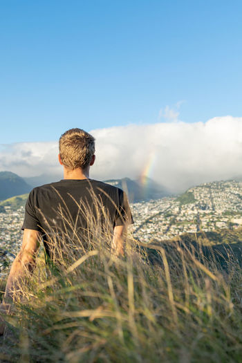 Rear view of man looking at rainbow against sky