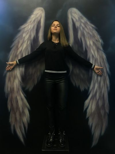 Young Woman Standing Against Angel Wings