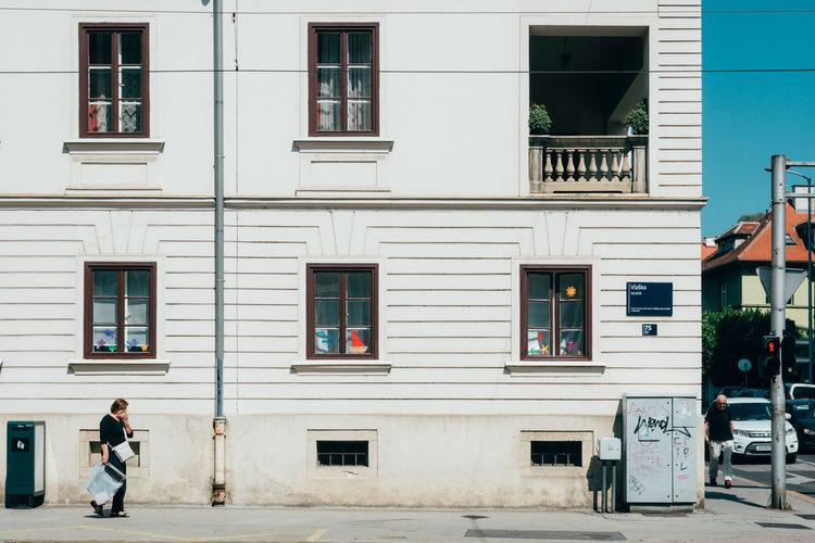 Full Length Of Man Walking On Street By Building