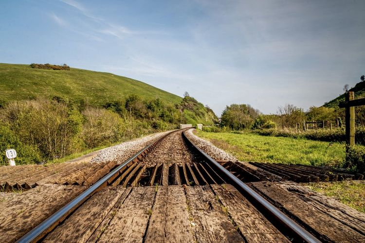 Railroad track passing through land against sky