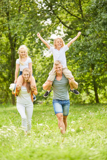 Portrait Of Happy Parents Giving Piggyback Ride To Children In Park