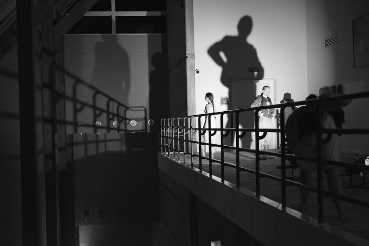 A performance artist and an audience member cast shadows as part of Ritual: (Sub) Urban Projections at the Hult Center in Eugene, Oregon on April 21st 2016. Blackandwhite Built Structure City Life Full Length Leading Lines Light And Shadow Performance Art Perspective