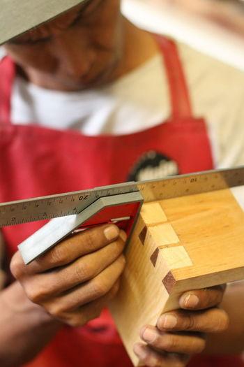 Close-up of carpenter measuring wood