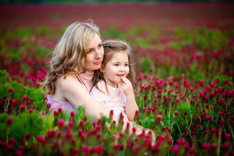 Cute girl with pink flower petals on land