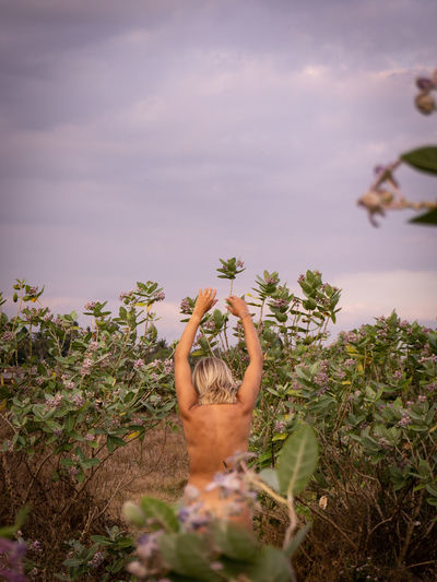 Rear view of sensuous naked woman standing by plants against sky