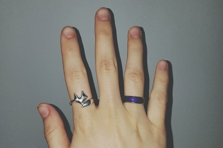 Cropped Hand Wearing Rings By Gray Wall