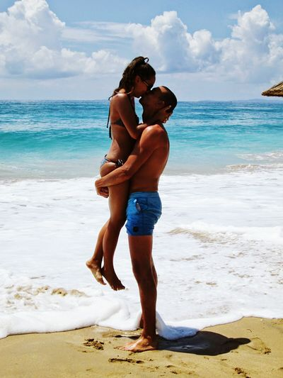 Young Couple Kissing At Beach Against Sky
