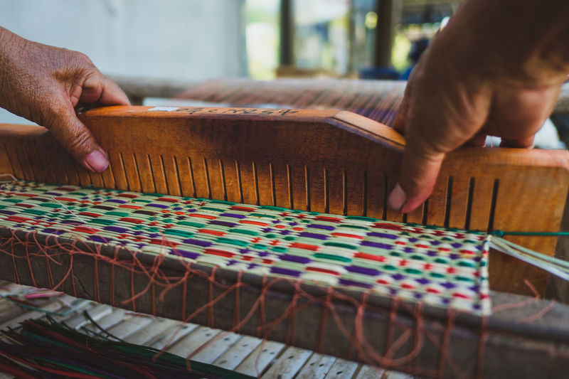 Cropped hands weaving loom