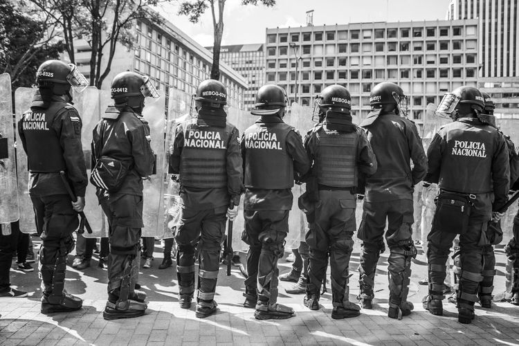 Rear view of police force standing in city