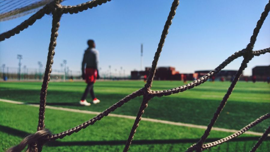 Man Seen Through Fence Walking On Field Against Sky