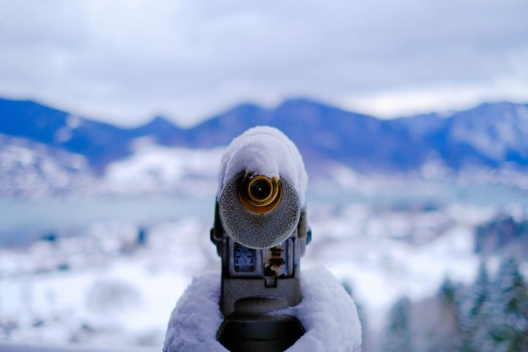 Close-up of snow capped binocular against mountain silhouette