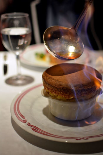 Spoon pouring caramel on flammable dessert souffle served on table
