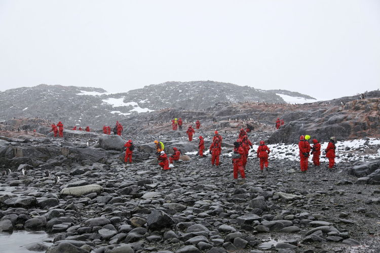 Workers on mountain against sky
