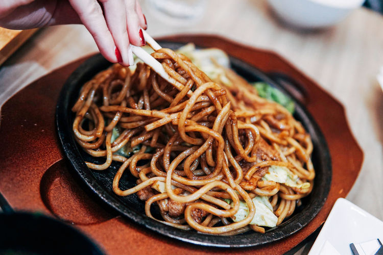 Close-up of hand holding noodles in plate on table