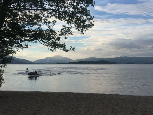 Beach Beauty In Nature Blue Sky Blue Sky And Clouds Clouds And Sky Day Jetski Lake LochLomond Mountain Mountain Range Nature On Your Doorstep Outdoors Scenics Tranquil Scene Tree Unrecognizable Person VisitScotland Water Waterfront Watersports