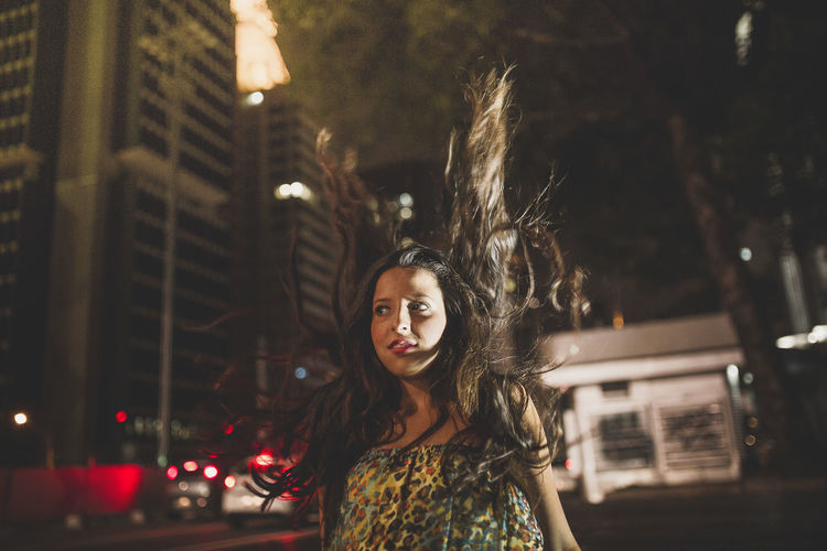 Portrait of woman standing in illuminated city at night