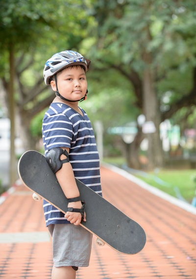 Portrait Of Boy Holding Skateboard In Park