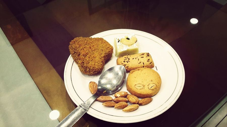 High angle view of cookies with almond and cutlet in plate