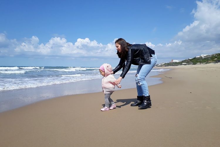 Mother and daughter at beach against blue sky