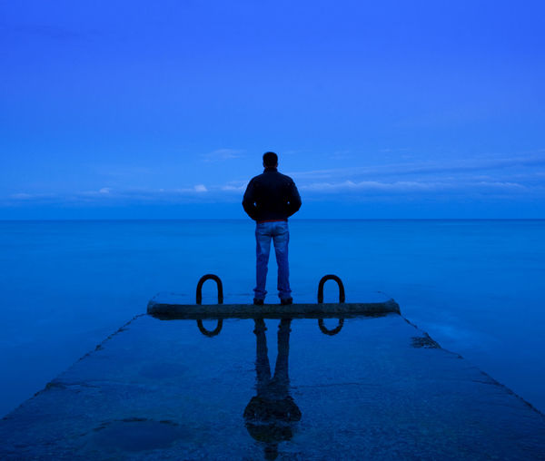 Rear View Of Man Standing On Pier In Sea Against Blue Sky At Dusk