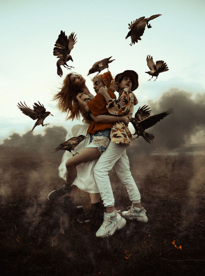 Birds flying by women embracing against sky
