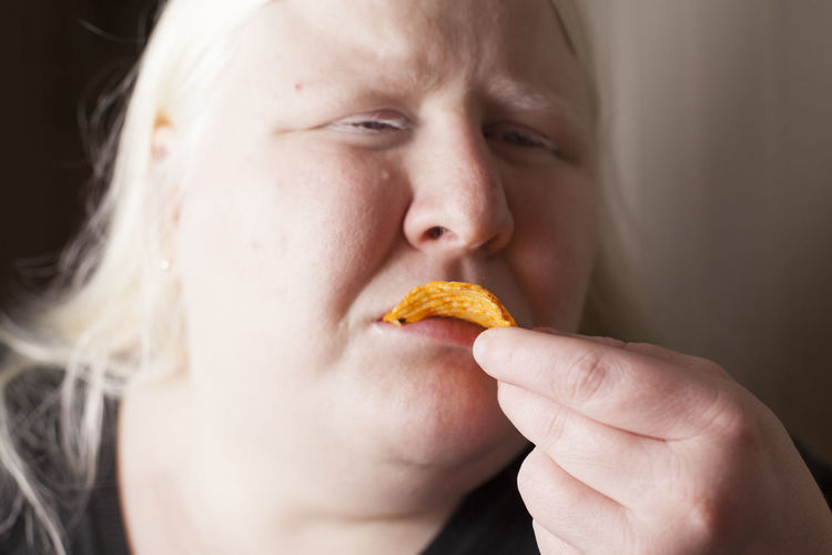 Close-up of woman eating potato chip