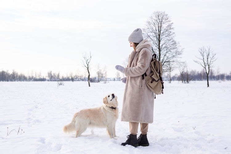 Woman with dog on snow covered field