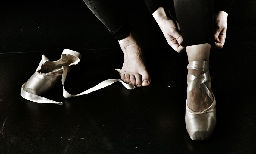 Low section of female ballet dancer wearing shoes on floor
