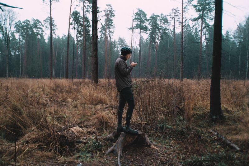 Man using mobile phone while standing on tree stump in forest