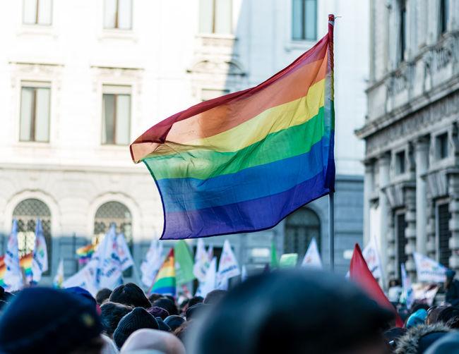 Rainbow flag in crowd against buildings