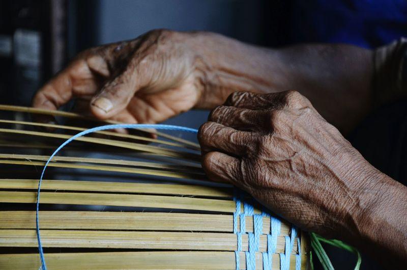 Close-up of hands making basket