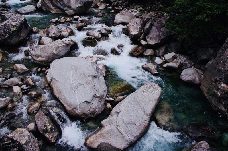High angle view of stream flowing through rocks in river