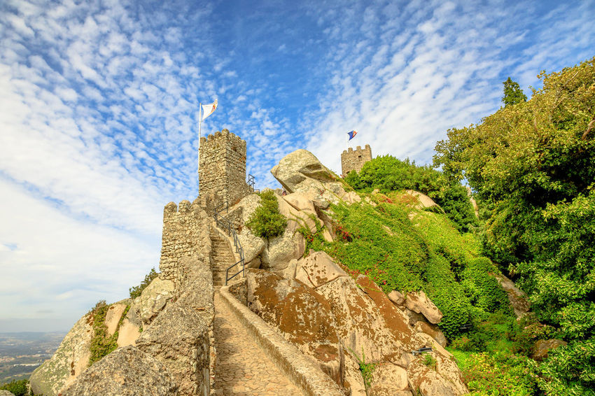Aerial view of ancient wall and tower of Castle of the Moors and Sintra valley. Castelo dos Mouros is medieval castle and Unesco Heritage on a hill above Sintra, Lisbon District, Portugal. Pena Palace and the ruins of Moors Castle are popular landmarks and major tourist attractions of the Cultural Landscape of Sintra as a World Heritage Site, Portugal. Portugal Sintra Castle Ruins Medioeval Cities Wall Tourism Flags Skyline Cityscape Palace Castle Ruin Aerial View Moors Castle Pena Palace Moors Sky Architecture Built Structure Cloud - Sky The Past History Nature Building Low Angle View No People Day Solid Building Exterior Ancient Travel Destinations Plant Travel Rock Rock - Object Outdoors Ancient Civilization