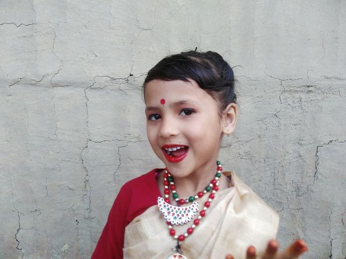 Portrait Of Smiling Girl Wearing Sari While Standing Against Wall