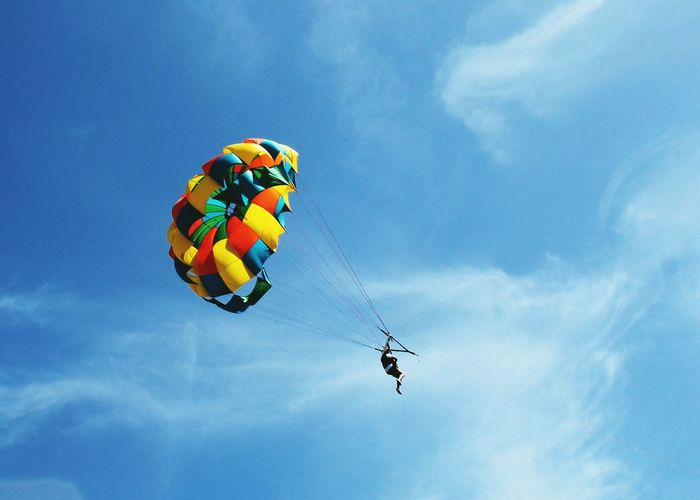 Low angle view of man parasailing against blue sky