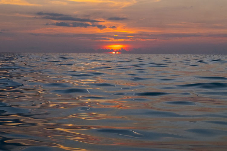 I ACTUALLY WENT INTO THE WATER WITH MY CAMERA WHICH IS NOT WATER PROOF JUST SO I CAN TAKE A PICTURE AS CLOSE AS POSSIBLE TO THE WATER SURFACE. I WANTED TO MAKE YOU FEEL WHAT I FELT IN THIS MAGICAL MOMENT. Beauty In Nature Cloud - Sky Horizon Horizon Over Water Idyllic Nature No People Non-urban Scene Orange Color Outdoors Reflection Romantic Sky Scenics - Nature Sea Sky Sun Sunset Surface Level Tranquil Scene Tranquility Water Waterfront