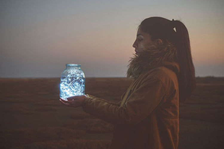 Side view of woman holding lights in jar against sky during sunset