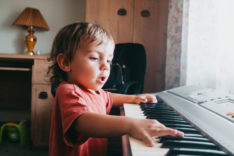 Cute boy playing piano at home