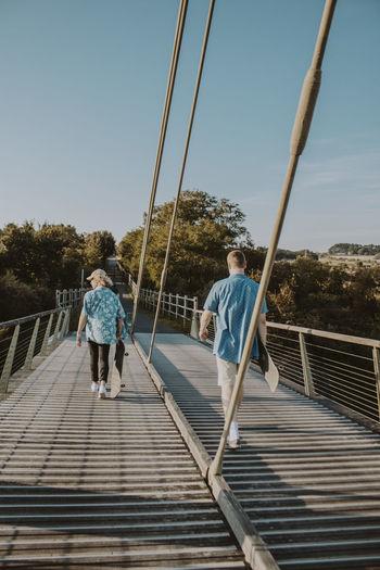 Rear view of people on footbridge against sky