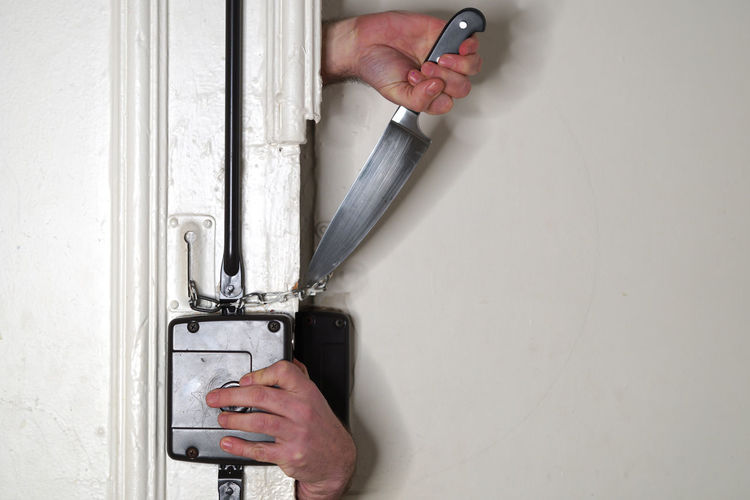 Cropped Hands Of Thief Cutting Door Chain With Knife